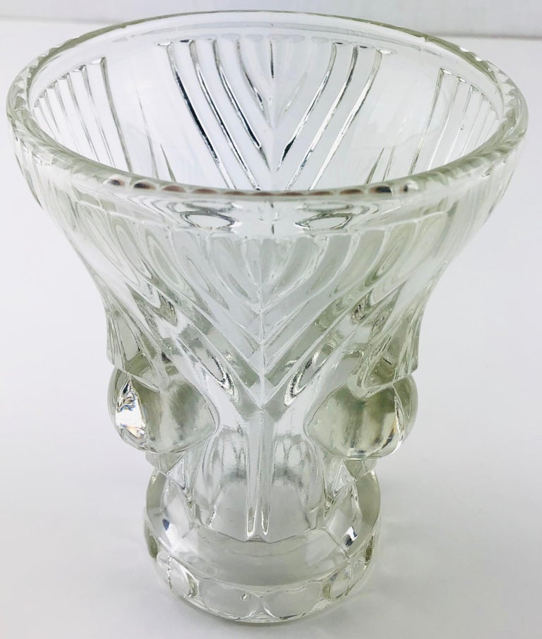 An exquisite small French Art Deco pressed glass vase. Adorned with 1920s-1930s period details, attributed to Lalique. Unmarked.   The glass is very clear, however, it was challenging to capture the clarity in the photographs.   Pressed glass is