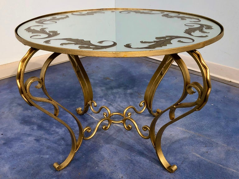 Very elegant French Art Deco round coffee table in gilded iron, with a decorated mirror on the top, 1950.