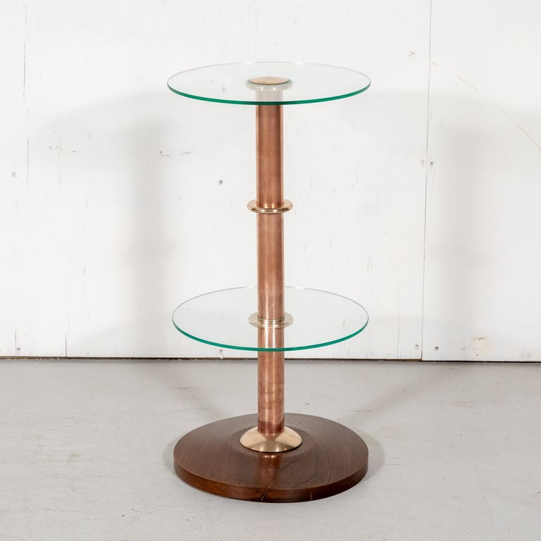 French Art Deco drink occasional or side table, circa 1930s, having a solid chestnut base and copper stem with a round glass top, glass shelf, and brass accents. The perfect size for a drink or an orchid, this sleek and chic drink table adds a