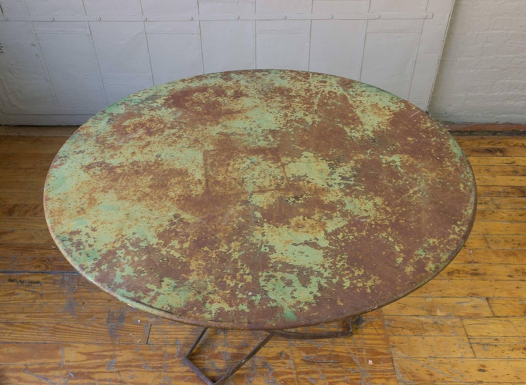 A very unusual Art Deco garden table, with traces of original paint on the metal top. The base is compose of intertwining iron sections that create an interesting sculptural pattern, French, circa 1920.