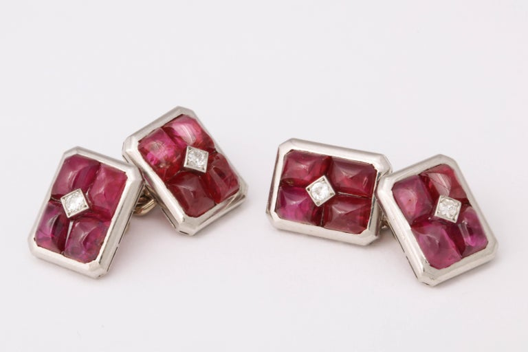 Four cabochon rubies surround a central diamond. Set in platinum. Made in France c. 1935.