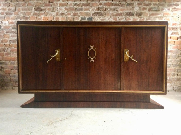 A magnificent midcentury French Art Deco walnut credenza, manufactured in France early 1950s, the rectangular top over three cupboards each with swirly Art Deco handles opening to reveal adjustable shelves within and fitted drawers to each of the