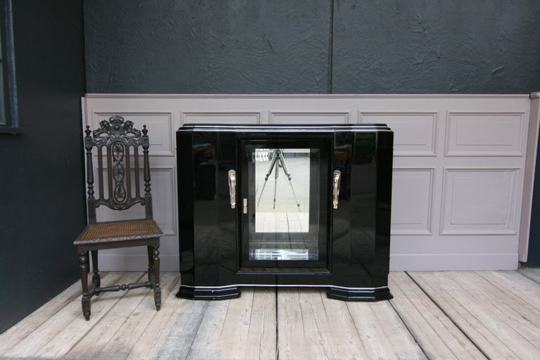 Original Art Deco sideboard from France in black high gloss, unrestored. Left side and right side, each with a door with a shelf behind it. In the middle is a glass door with faceted cut glass. Mirrored behind, rear wall and floor. 2 glass