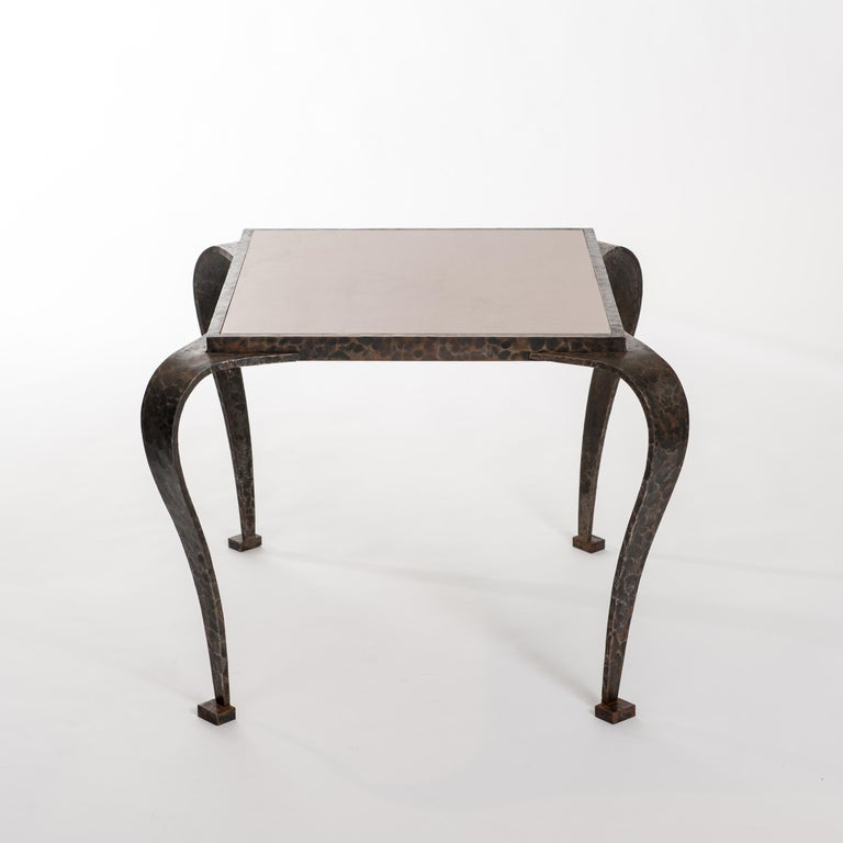 Impressive iron Art Deco side table with hammered surface and elegant curved legs. The side table displays an extraordinary impressive look due to its hand forged, hammered surface and the marble top. The rusty brown-grey color of the waxed iron