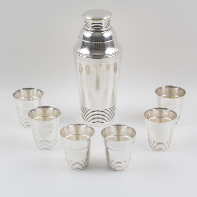 Elegant French Art Deco silver plate barware serving set by Silversmith Boyer et Fils, Paris. Three sectioned designed cylindrical cocktail or Martini shaker with removable cap and strainer, compliment with six silver plate cocktail cups with same