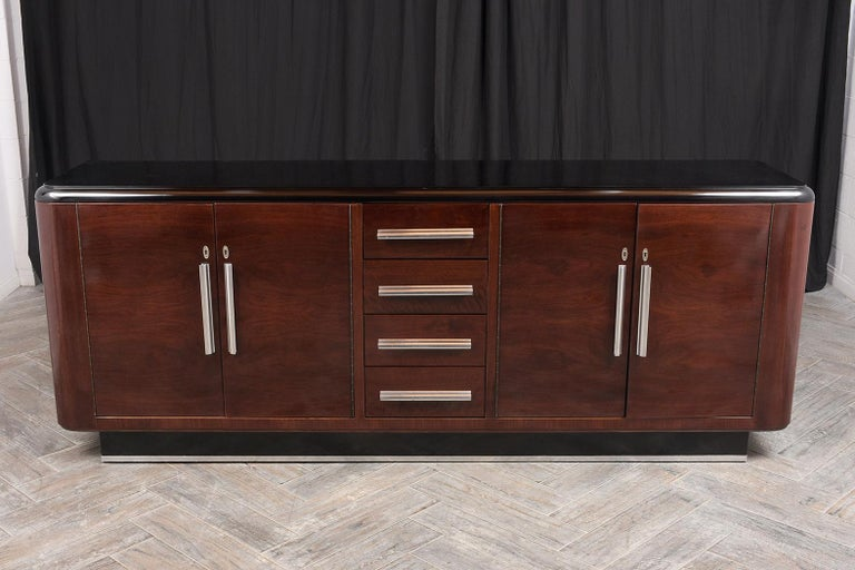 This 1930s French Art Deco-style rosewood buffet has been fully restored. It is newly stained dark mahogany and black color combination with a lacquered finish. This buffet has a wooden top with rounded side design, four small center drawers, and