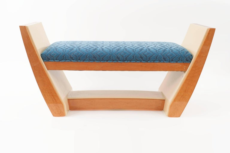 French Art Deco style (modern) maple and sycamore wood bench with flared side arms and blue upholstered seat with a slight arch design stretcher (in stock-can be customized).