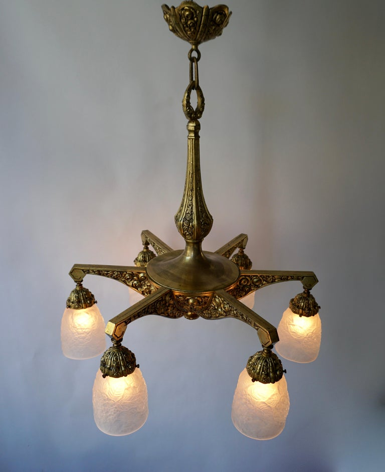 French Art Deco style bronze chandelier with floral motifs from the 1930s. Six bronze arms, each with frosted glass shade and a socket for E 27 light bulb.
