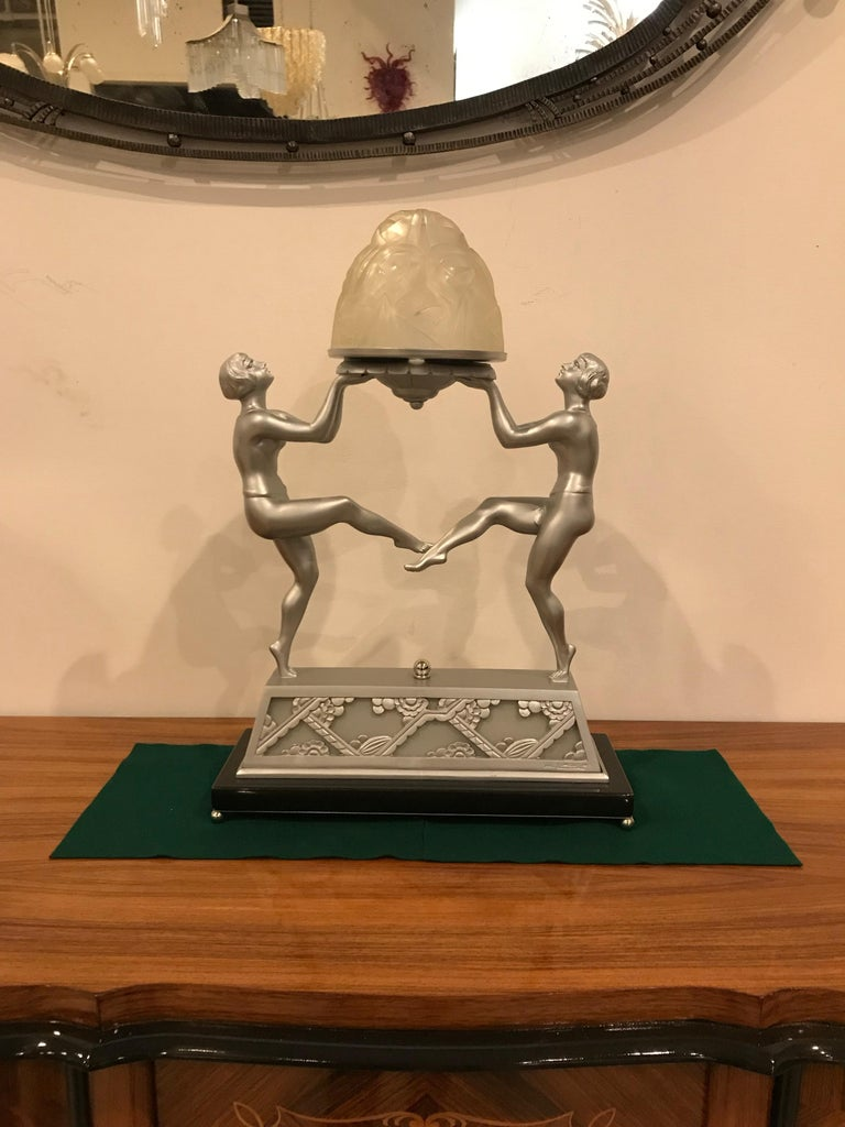 Rare French Art Deco table lamp. Clear frosted glass globe having floral motif signed by Degue. Held on a nickeled bronze decorative design frame signed on the base by Limousin. The Pair of Deco dancing females figures hold the beautiful two tier