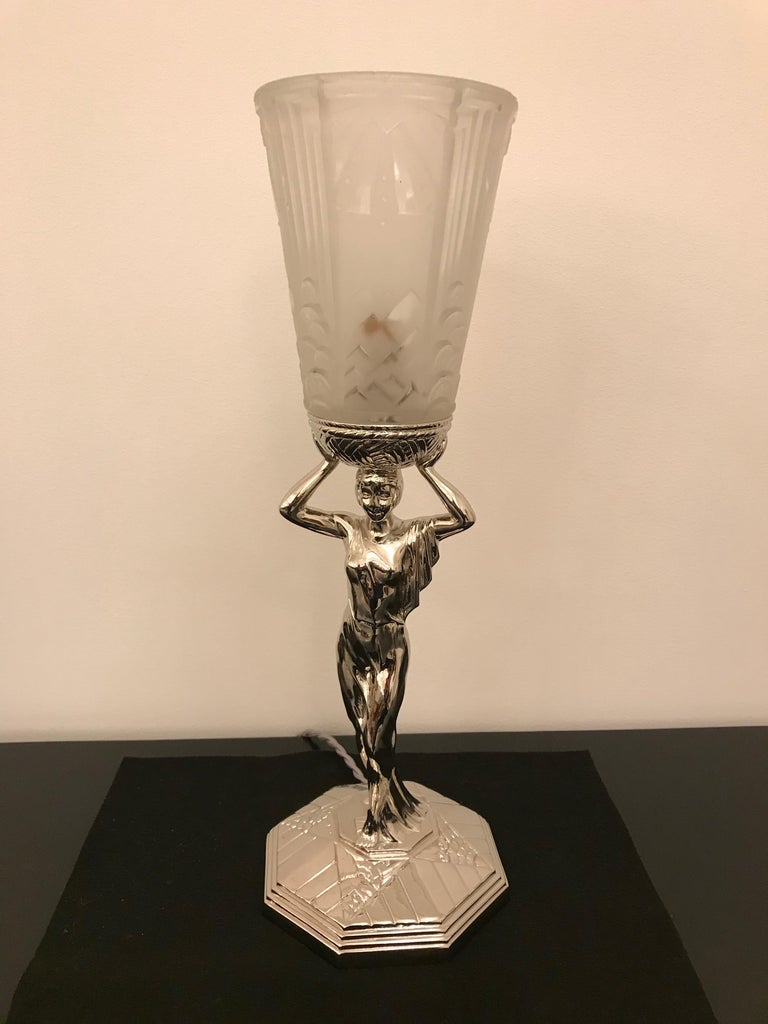 Beautiful French Art Deco table lamp. Clear frosted glass shade having geometric motif signed by Muller Frères Luneville. Held on a nickeled female decorative Deco design lamp base. Has been rewired for American use with one candelabra sockets. Has