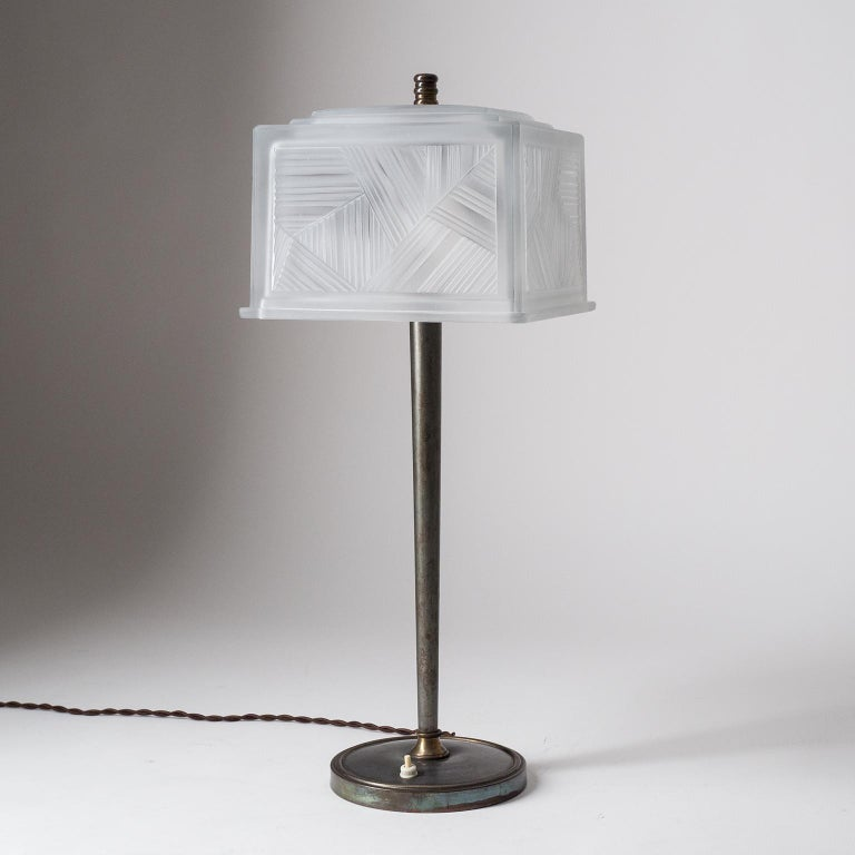 Very rare tall table lamp by Sabino, Paris, circa 1930. Slender, dark patinated, hardware with a heavily textured glass shade. Very thick glass with geometric pattern and a satin finish. Very good original condition with two brass and ceramic E27