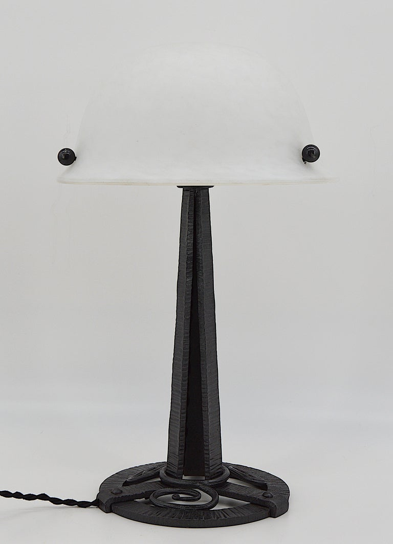 French Art Deco table lamp, France, circa 1925. Glass and wrought iron. Very nice lampshade in white mottled glass. Double glass, white enamels are applied between the two layers. On its wrought iron base. Same period as Daum, Schneider, Muller