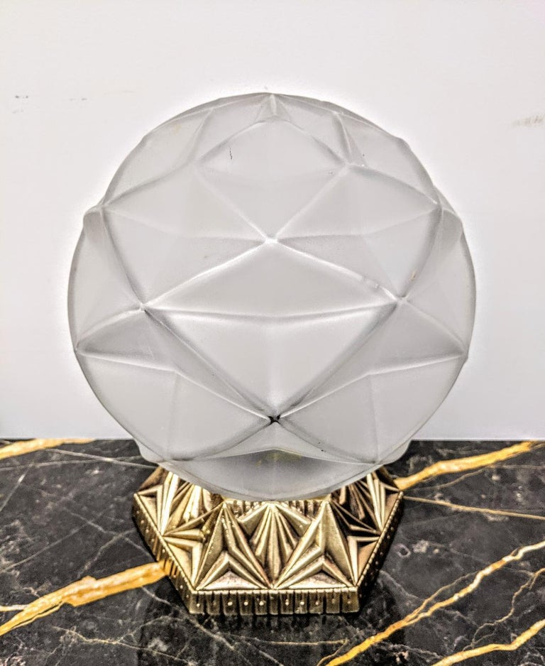 A French Art Deco geometric design table lamp. The glass shade is frosted with polished details in great condition, modest wear commensurate with age. Mounted in a decorative bronze base in its original patina. Table lamp has been rewired for U.S.
