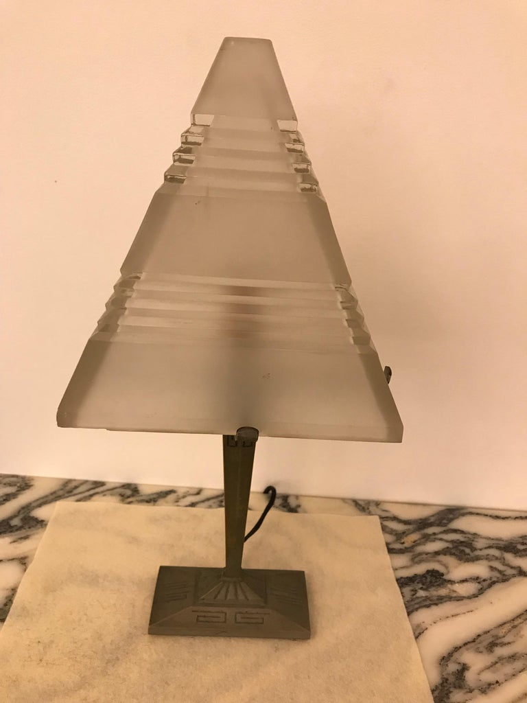 French Art Deco table lamp with triangular glass shade having geometric motif. The glass sits on a brass geometric base. Has been rewired for American use with one candelabra socket. Max watt is 60 watts. The frame can be re plated upon request.