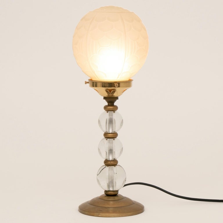 An Art Deco table lamp with brass and glass ball column, and original frosted glass globe shade with moulded Art Deco design