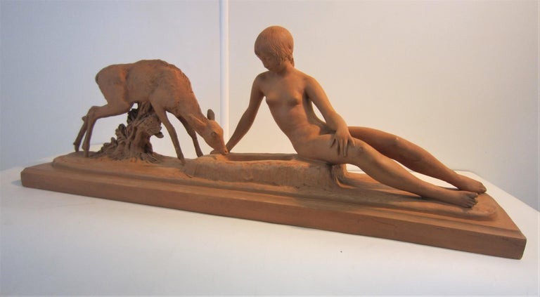A fine signed original French Art Deco terracotta sculpture of a naked young woman seated on a rectangular shaped self plinth. The bare chested female figure in a semi reclining pose is portrayed with a fawn drinking out of a trough by her