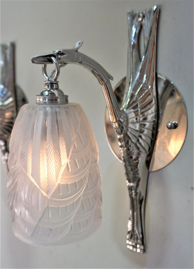Pair of bird design nickel on bronze wall sconces with feather design glass shades by Charles Scneider.