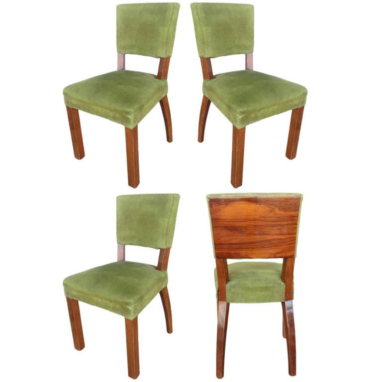 Set of six French Art Deco walnut dining chairs with large decorative wood backboard and dark green coverings,   France, circa 1920.