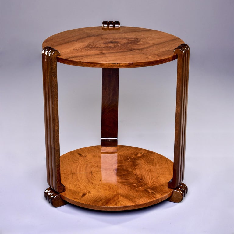 Circa 1930s French round side or center table features a highly figured walnut veneer top and base with contrasting darker reeded side supports and feet. Unknown maker. Professionally refinished.