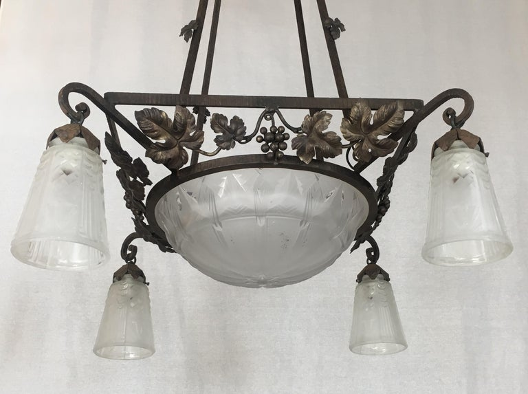 A stunning original classic Art Deco light fixture by Muller Frères. This eye-catching wrought iron chandelier features a frosted and etched glass dome and trumpet shades with geometrical forms. Handmade in the early 20th century, circa 1930. This