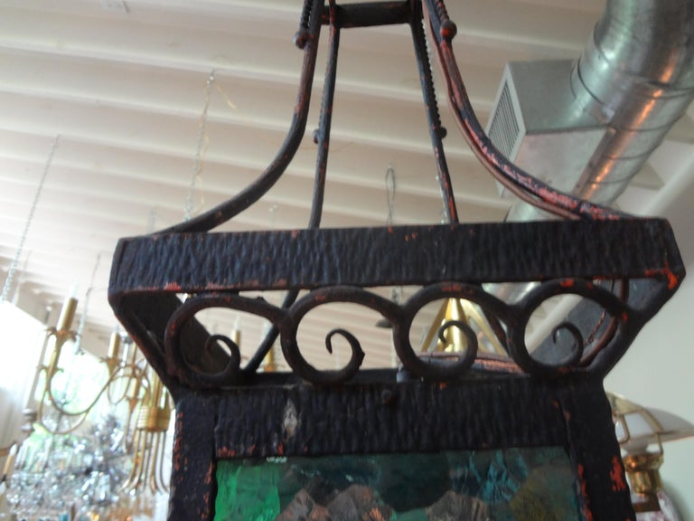 Great period French Art Deco hand forged wrought iron lantern. This beautiful French lantern has subtle deco accents with lovely multicolored glass panels. Featured French iron lantern or pendant has been newly wired for the U.S. Market and dates to