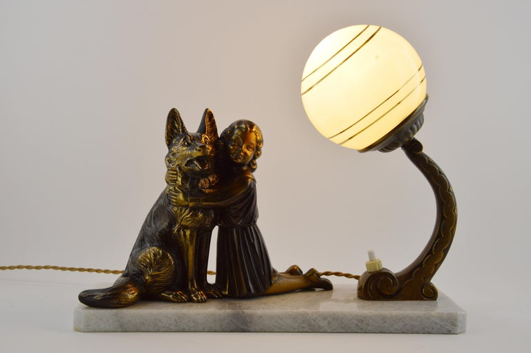 French Art Deco table lamp, 1930s. Spelter German shepherd and little girl sculpture on its marble base. Green double glass shade with golden concentric circles. Delivered wired for your country (US, EU, Australia, etc...).