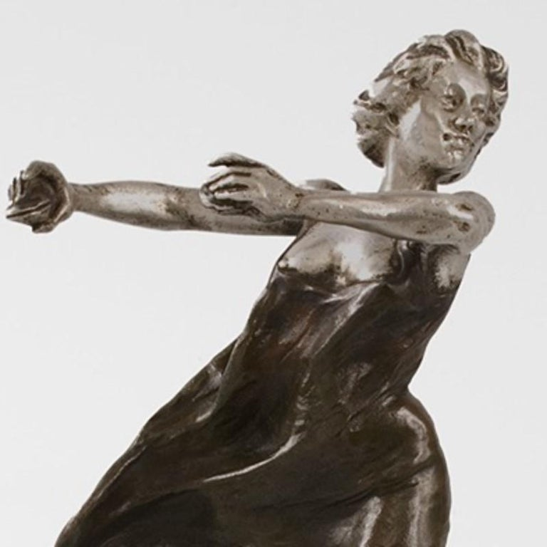 A French Art Nouveau bronze sculpture of a Castanet dancer in motion with flowing gown by Rupert Carabin. A French Art Nouveau bronze sculpture of a castanet dancer in motion with flowing gown by Rupert Carabin. This barefoot woman holds her