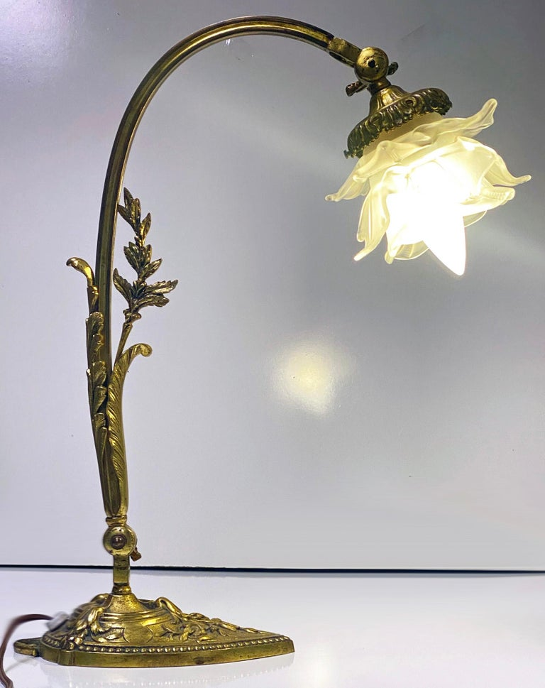 French Art Nouveau table desk lamp, circa 1920. The gooseneck bronze stand with applied foliage floral decoration, supporting a delicate, frosted white rose petal glass shade, adjustable neck and base. Measure: Height 16.5 inches.
