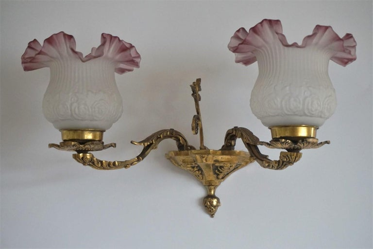 A lovely Art Deco brass two-light wall sconce decorated with foliage, frosted art glass shades, France 1930s. Very good condition, with wonderful patina, rewired Measures: Width: 18.50 in (47 cm) Height: 11 in (28 cm) Depth: 10.75 in (27