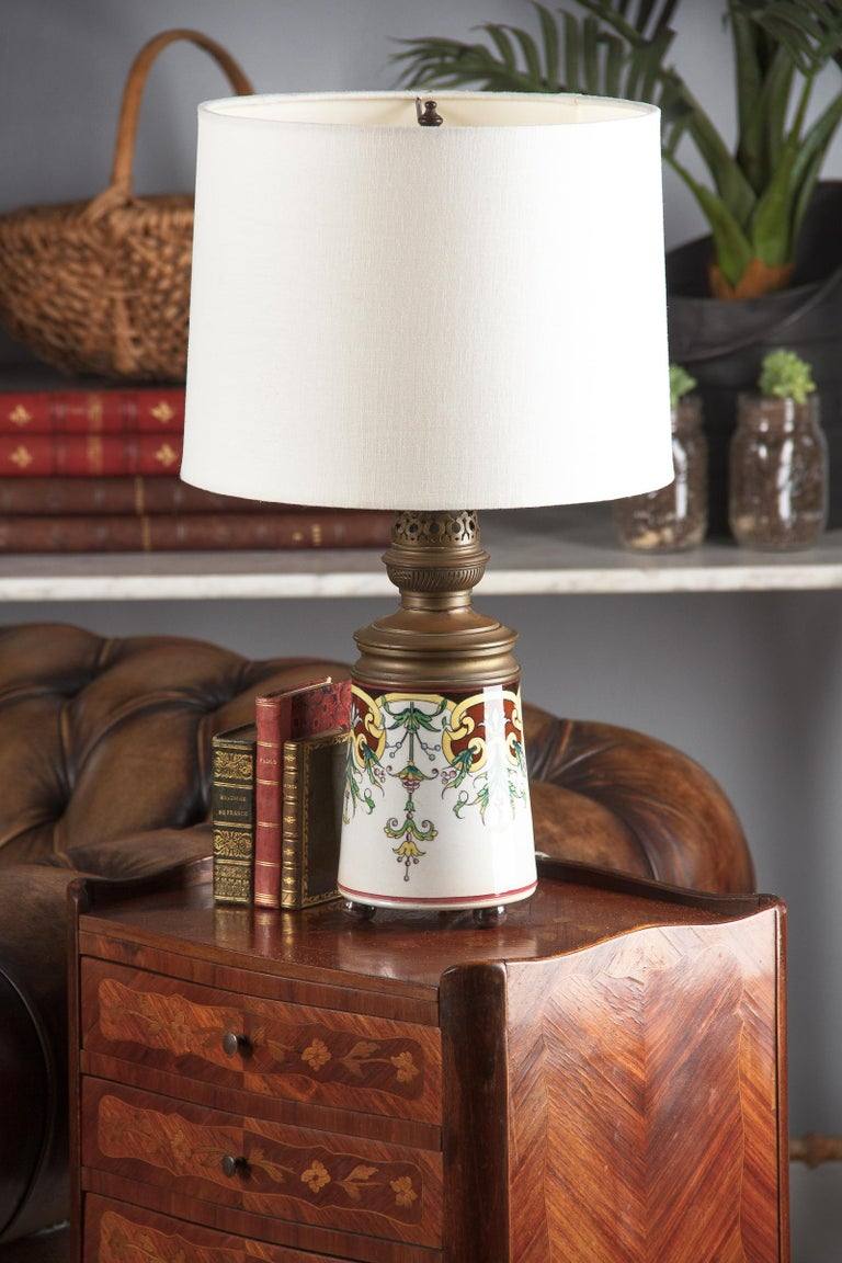 An Art Nouveau table lamp, once an oil lamp and now electrified. The ceramic reservoir with hand painted arabesque motifs is by Sarreguemines. The brass burner is by Augusta Brenner. The actual shade is 12