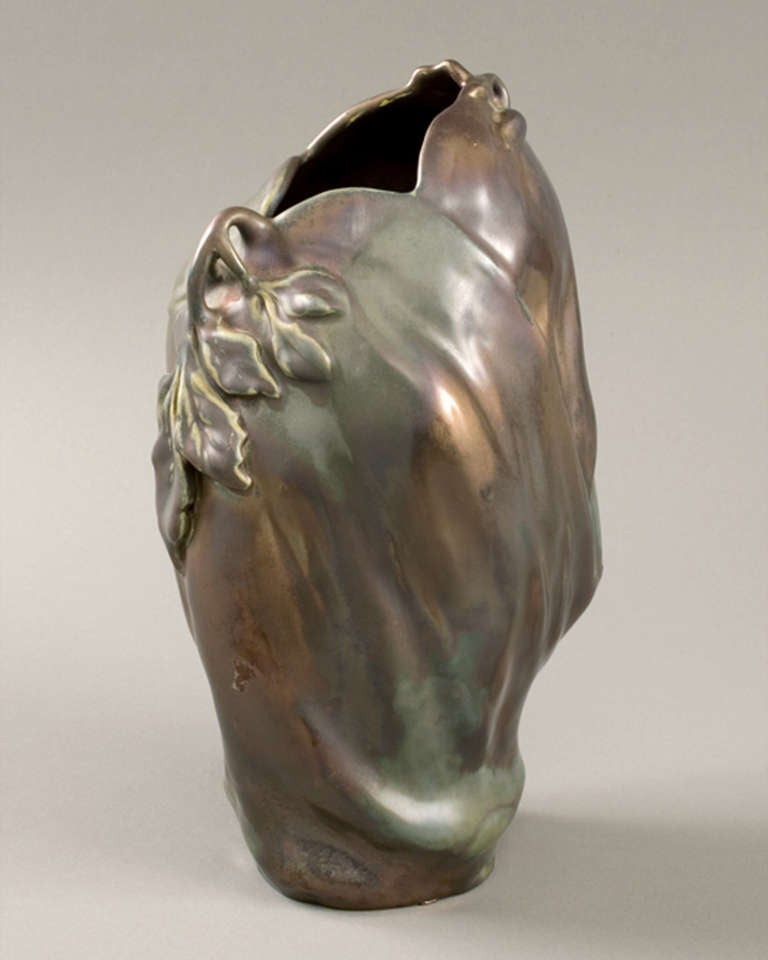 "A French Art Nouveau ""Eggplant"" vase, by Keller and Guérin, following a design of Ernest Bussière, featuring iridescent gold, brown and green glazes.   The vase has gentle folds and is decorated with applied curving stems holding elongated leaves,"
