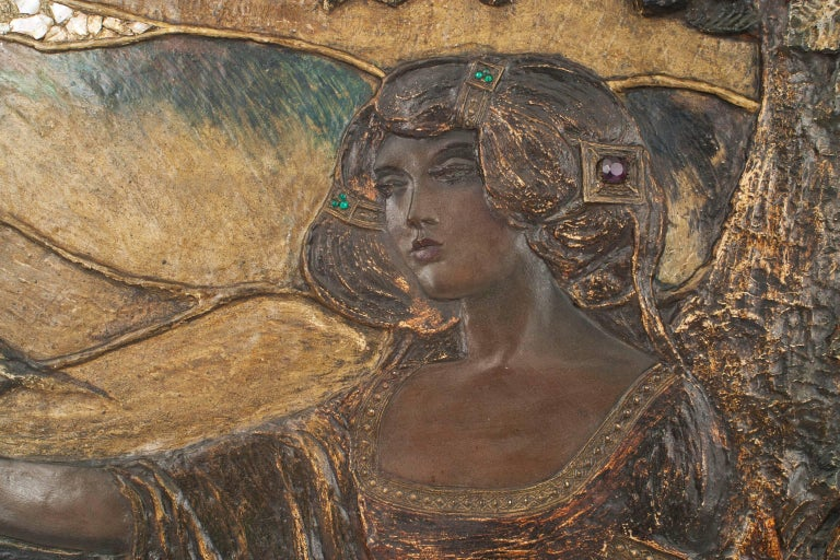 French Art Nouveau dark polychromed plaster horizontal wall plaque with a carved relief of a woman inlaid with mother-of-pearl and glass cabochons in an oak frame (signed: SF).