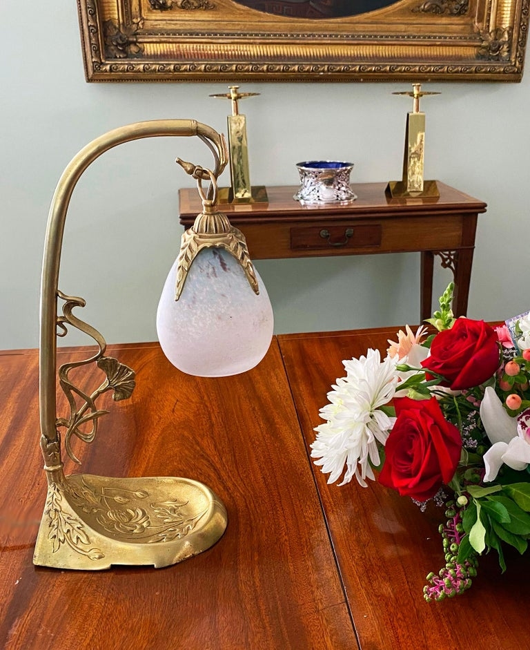 French Art Nouveau desk table lamp by Charles Schneider (Epinay-sur-Seine, Paris), France, ca.1920 on stylized bronze base. The glass shade was made of blown double glass with powders between both layers. Measures approximately 15.75 x 8.75 x 5.25