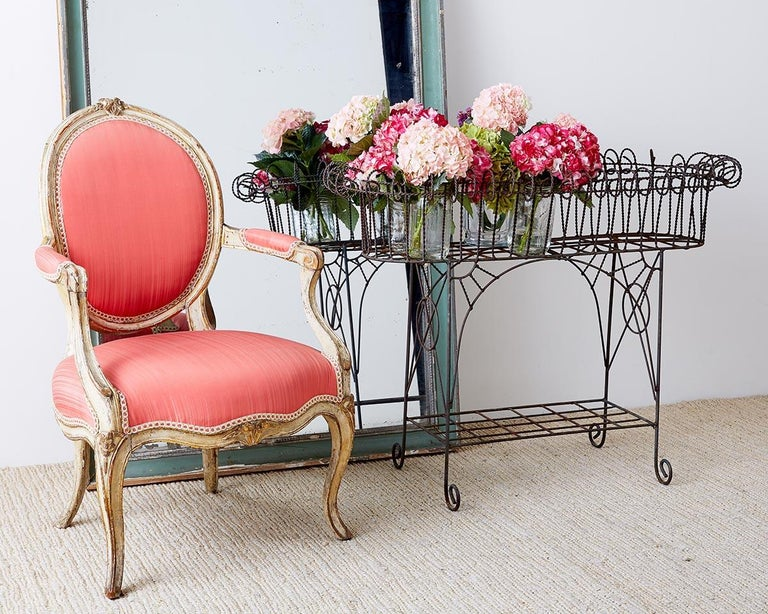 Sculptural French art nouveau plant stand constructed from iron with a faux-rope twisted wire top. The stand has a lower shelf with decorative circles and spandrels on each side ending with scrolled feet.