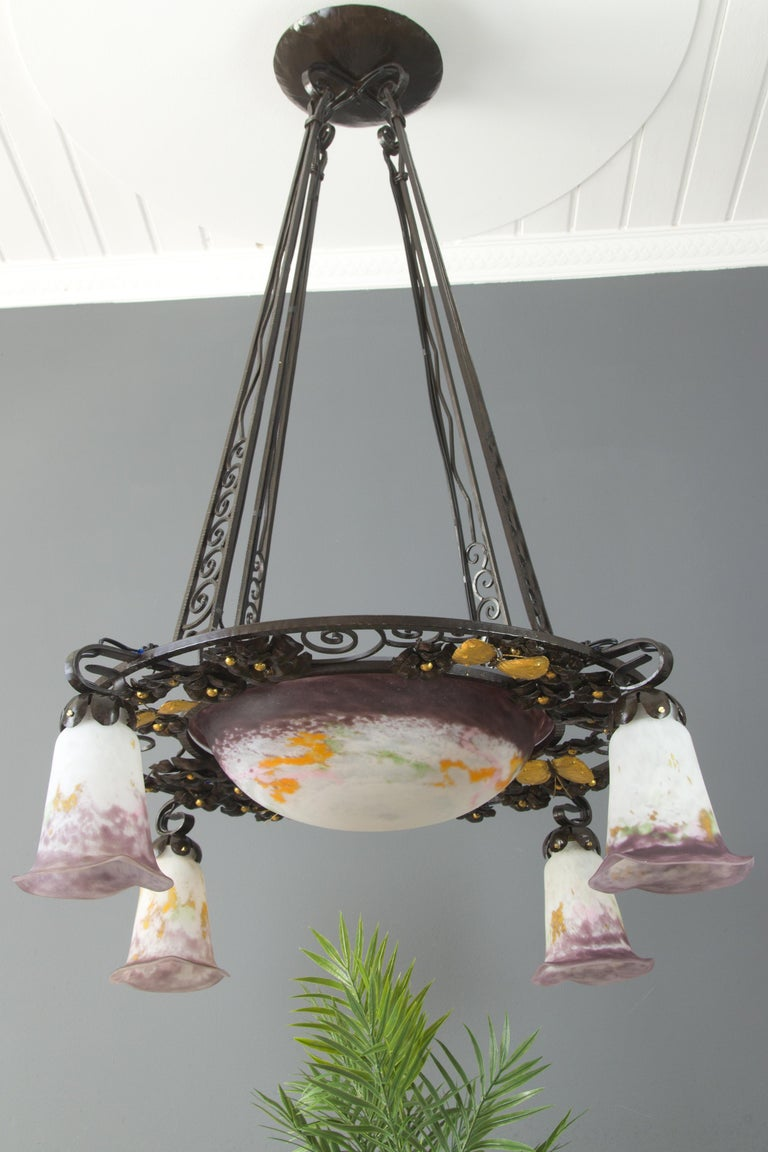Stunning and large French Art Nouveau chandelier in purple, yellow, green, and white glass paste, consisting of a central bowl and four tulip sconces by Verreries d'Art Lorrain. Glass shades signed