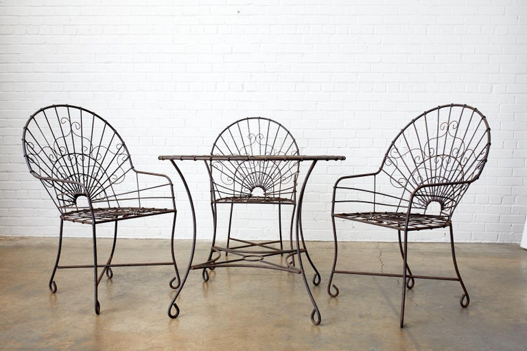 Charming French Art Nouveau garden patio dining table. Constructed from wrought iron and decorated with wire scrolls on the top in a sunburst pattern design. The gracefully curved legs are conjoined by a stretcher. The legs end with looped feet.