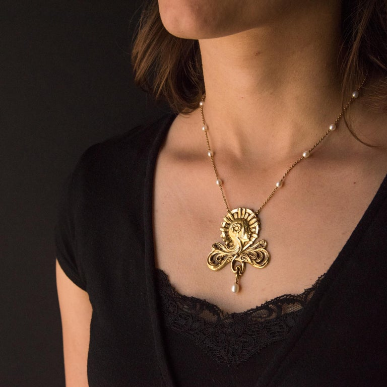 Baume creation - Unique piece. Necklace in 18 carat yellow gold, eagle head hallmark.  Featuring a woman's head, her hair blends into an openwork design engraved beneath. She wears a golden flower in her hair. The design is completed with an
