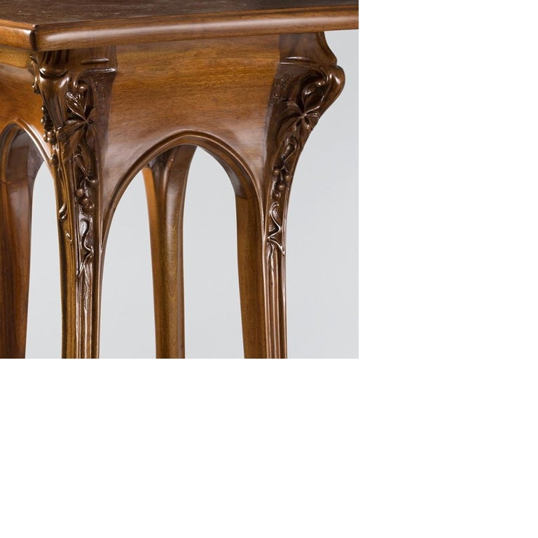 A French Art Nouveau walnut 3 tiered pedestal by Louis Majorelle, featuring a rotating tray on the top. Leaves and berries adorn the upper portion of the legs. The gently curving legs are also deeply carved, circa 1900.  Pictured in, Louis