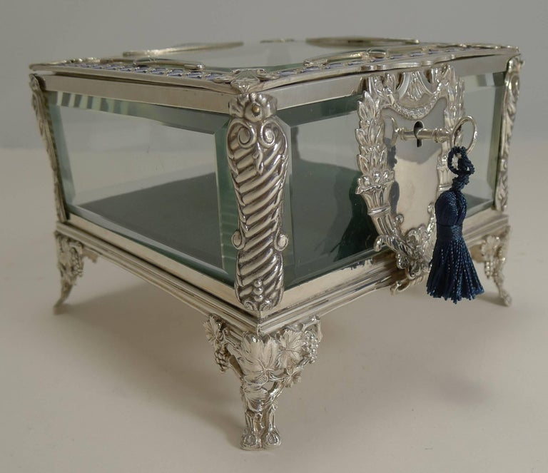 An absolutely splendid French jewellery casket made from silver plate, retaining the original panels of cut-glass.  The box stands on four highly decorative feet with a grapevine decoration and the front having the most grand escutcheon housing