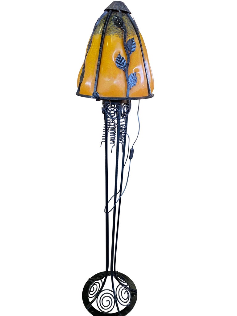 A wonderful French Art Nouveau style standard lamp, 20th century. The stands are handmade in wrought iron with black finish patina and hammered with floral pattern. The metalwork is of excellent quality. Crowned with bright colored shades in