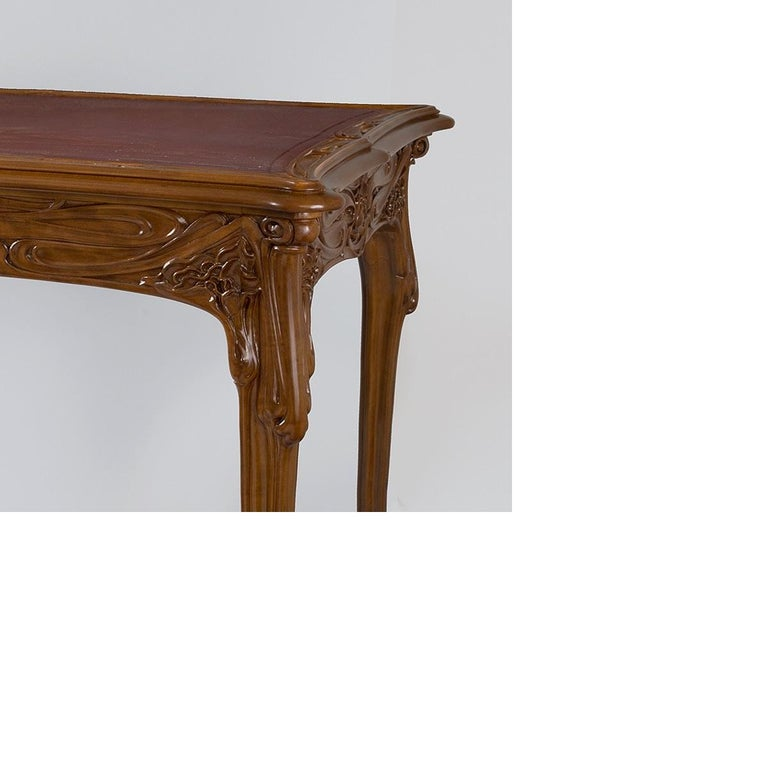 An exceptional French Art Nouveau fruitwood table by Edouard Colonna with a black felt center, flanked by a scalloped decoration of vegetal carvings. The slightly curved legs adorn a rich decor of flowers and plants in relief, circa 1900.