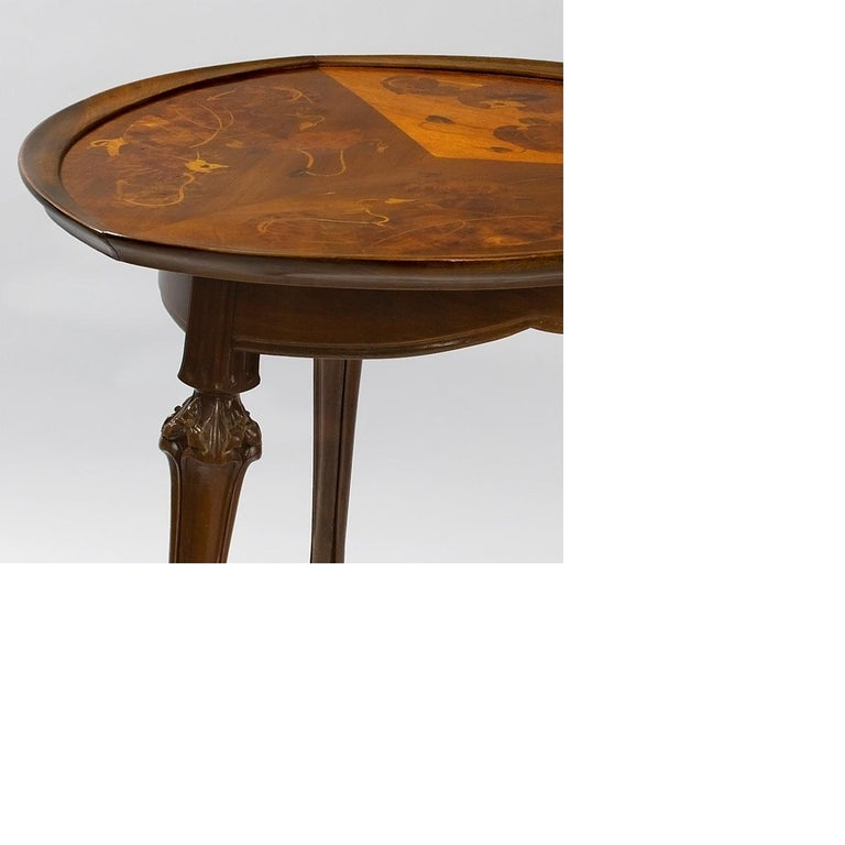 A French Art Nouveau mahogany salon table with fruitwood marquetry by Louis Majorelle. The table top is decorated with leaves and vines. The legs have carved flowers, circa 1900.  Provenance Property from the Geyer Collection Louis C. Tiffany