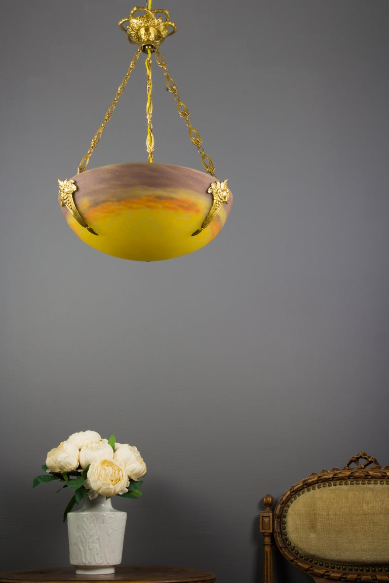 """This adorable French Art Nouveau period pendant chandelier features a mottled """"Pâte de verre"""" glass shade in yellow, purple and orange color, signed """"GV de Croismare"""" by Muller Freres, hung at an ornate bronze fixture with one socket for E27 light"""