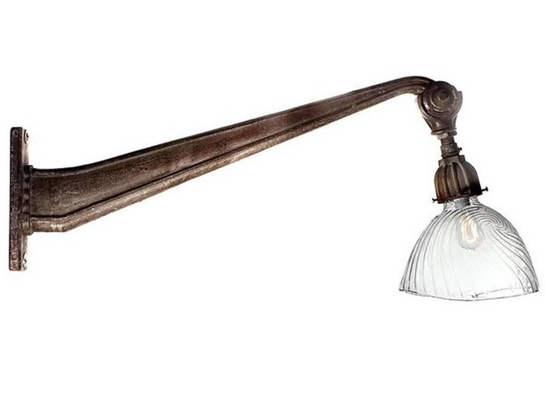 This French arm is beautiful cast iron with an original patina. The end of the arm has an angle adjustment to point the lamp and shade. The look is very clean and a bit Art Deco. The shade is one of the largest mercury glass examples that was ever