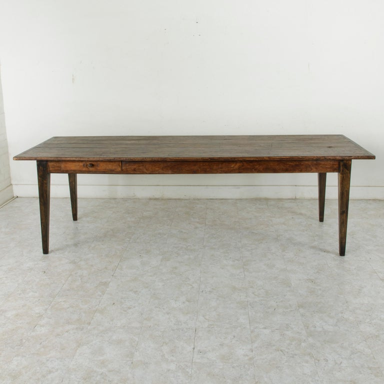 This turn of the 20th century artisan-made farm table is from the region of Le Perche, a Sub-region of Normandy, France. Its oak top is constructed of five planks of wood and measures 103 inches long and 36 inches wide. A pull out / pull-out cutting