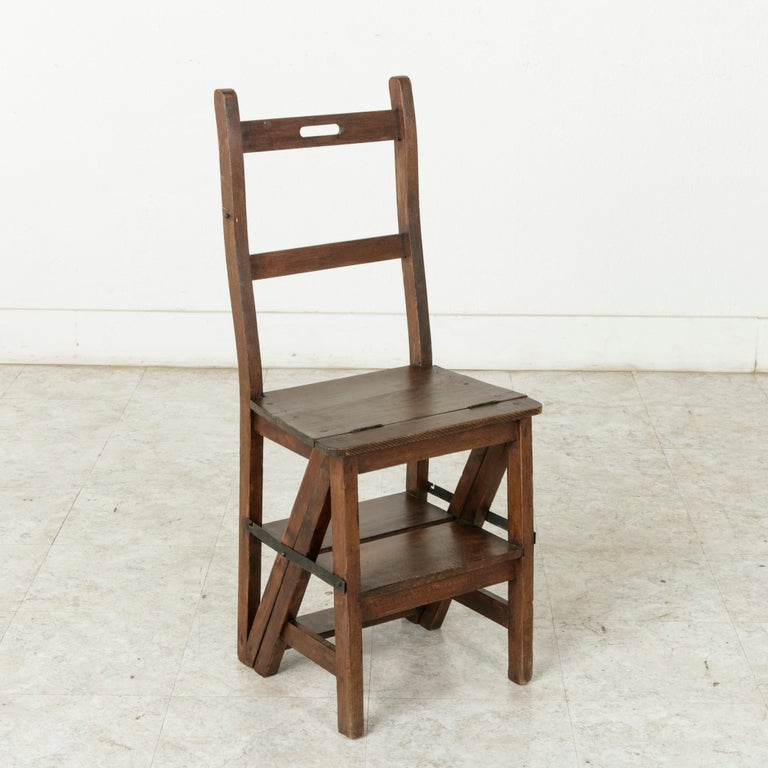 From the region of Provence in southern France, this artisan-made oak folding chair is hinged so that it can convert into a step ladder. Iron straps with hooks allow for the piece to be secured in place both as a chair or ladder. When used as a