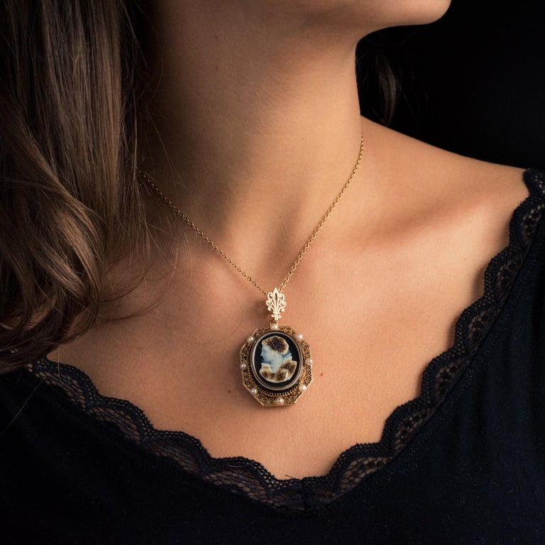 Brooch / pendant in 18 karat yellow gold, eagle's head hallmark. Octagonal shaped with an openwork circle pattern and studded with natural pearls, this pendant holds a cameo on 4-layered agate representing the left profile of a bust woman. The back