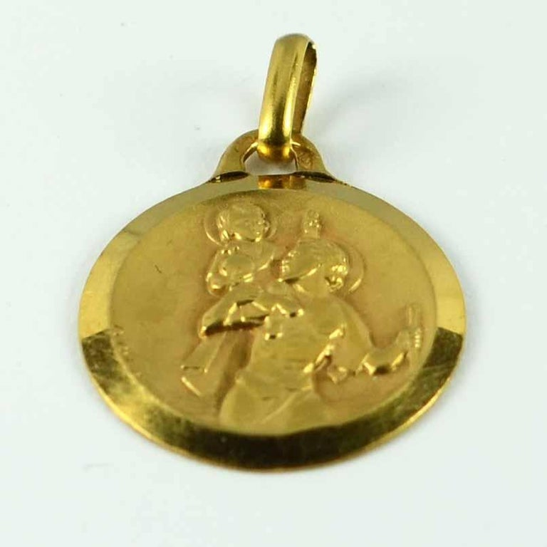 A French 18 karat (18K) yellow gold charm pendant or medal designed by Augis depicting St Christopher carrying the infant Christ across the river. This unusual version is modelled in high relief for a strongly three-dimensional feel, has incredible
