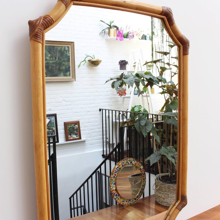 French bamboo and rattan vintage wall mirror, circa 1960s. This mirror has a delightful Asian-inspired shape formed by the bamboo frame and held together with rattan ties on the edges and curves. There is a characterful, aged patina and some