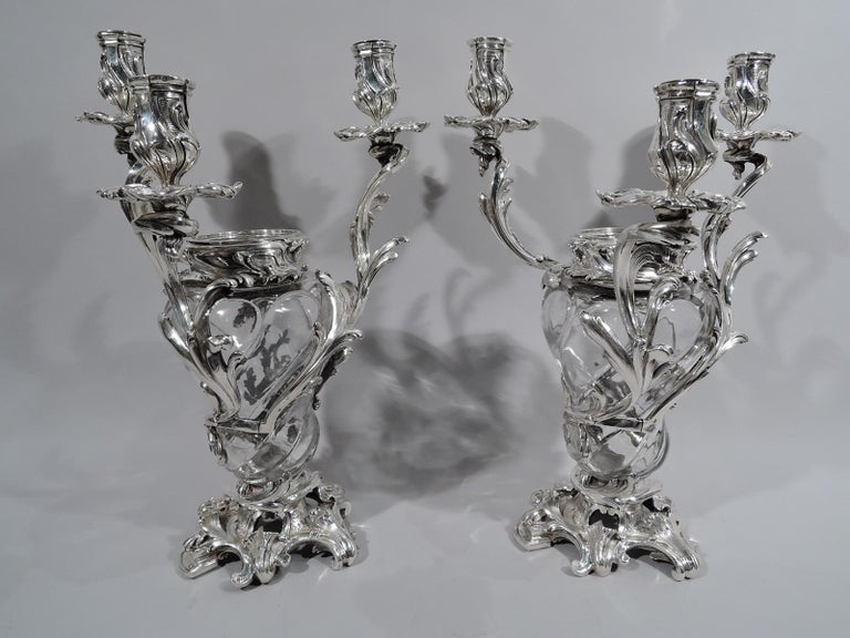 Set of 4 French Belle Époque crystal and silver vase candelabra, circa 1890. Each: Lobed baluster crystal vase with wraparound silver leafing, each terminating in single leaf-wrapped socket with petal wax pan. More leafing applied to rim. Open